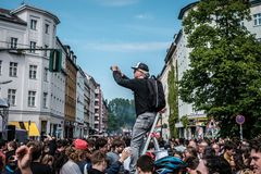 Person on ladder taking picture of crowded street festival on labor day in Berlin, Kreuzebreg. Berlin, Germany - May 01, 2019: Person on ladder taking picture of royalty free stock photography