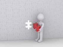 Person and last puzzle piece of wall. Person is holding the last puzzle piece of a big wall of many pieces Stock Image
