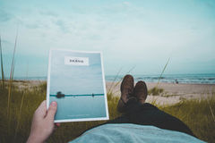 Person Laying on Green Grass Field Near Beach Reading Journal Stock Images