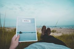 Person Laying on Green Grass Field Near Beach Reading Journal Stock Image