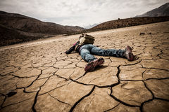 Person lays on the dried ground Royalty Free Stock Images