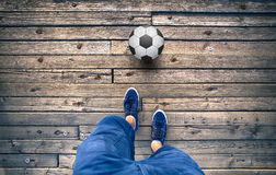 Person legs with soccer ball on wooden floor. Point of view of a man legs with soccer ball on old wooden tile floor stock photos