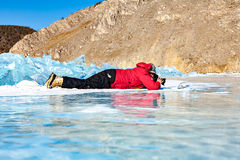 The person lies on the ice and the ice photographs. Royalty Free Stock Photos