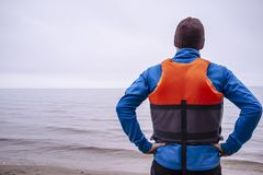 Person in life jacket lies a sandy beach on the lake. With waves stock photo