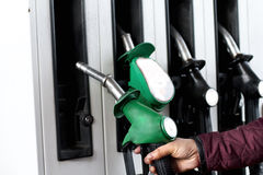 Person lifting Fuel pumps at petrol station Stock Images
