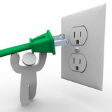 Person Lifting Power Plug to Electrical Outlet Royalty Free Stock Photo