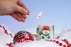 Person Lighting Christmas Candle With Decorations Around It Royalty Free Stock Image