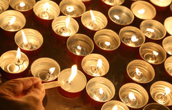 Person lights a candle during the religious ceremony. Hand of the person who lights a candle during the religious ceremony Royalty Free Stock Photos