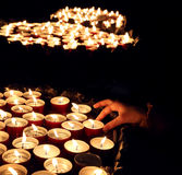 Person lights a candle during the religious ceremony. Hand of the person who lights a candle during the religious ceremony Royalty Free Stock Photo
