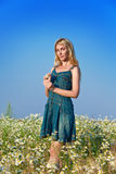 The person with a long fair hair in a blue dress costs in the field of camomiles against the blue sky Stock Photography