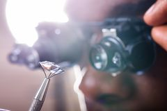 Person Looking At Diamond With die Loupe overdrijven royalty-vrije stock afbeelding