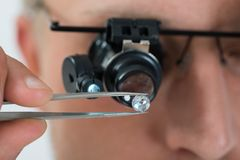 Person Looking At Diamond With Magnifying Loupe Royalty Free Stock Photo
