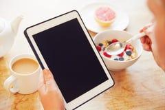 Person Looking At Digital Tablet enquanto comendo o café da manhã Fotografia de Stock Royalty Free