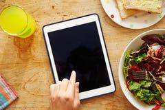 Person Looking At Digital Tablet stund som äter lunch Royaltyfri Foto