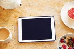 Person Looking At Digital Tablet terwijl het Eten van Ontbijt stock foto