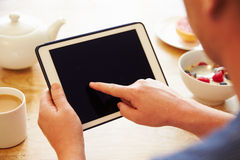 Person Looking At Digital Tablet Whilst Eating Breakfast Royalty Free Stock Photo