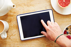 Person Looking At Digital Tablet Whilst Eating Breakfast Stock Image