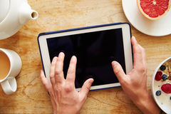 Person Looking At Digital Tablet Whilst Eating Breakfast Royalty Free Stock Images