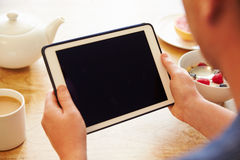 Person Looking At Digital Tablet Whilst Eating Breakfast Stock Photo