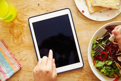 Person Looking At Digital Tablet Whilst Eating Lunch Stock Photo