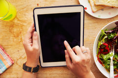 Person Looking At Digital Tablet Whilst Eating Lunch Royalty Free Stock Images