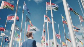 A person looks into a promising future. Conceptual clip against the background of clear sky and national flags of different countries stock video footage