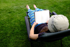 Person Lounging in Lawn Chair Relaxing and Reading Book Stock Image