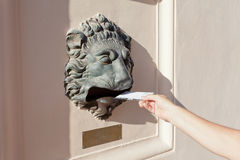 Person lowers the letter in a mailbox Royalty Free Stock Photo