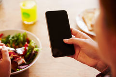 Person At Lunch Looking At To Mobile Phone Royalty Free Stock Image