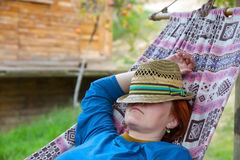 Person lying in Hammock at Patio of Wooden Rural Cottage Royalty Free Stock Photo