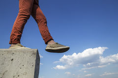 Person makes confident step with concrete wall on the white fluf Royalty Free Stock Image
