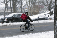 Person making delivery on bike during snow storm Royalty Free Stock Photo