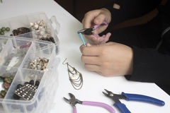 Person making jewelry with beads and other materials with tools. Person making jewelry using wire, chains and  beads and other materials with craft tools Royalty Free Stock Images