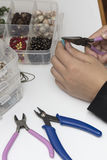 Person making jewelry with beads and other materials with tools. Person making jewelry using wire, chains and  beads and other materials with craft tools Stock Image