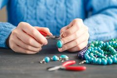 Person making jewelry using wire, chains and beads and other materials with craft tools Royalty Free Stock Photos