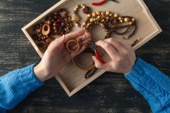 Person making jewelry using wire, chains and beads and other materials with craft tools stock image
