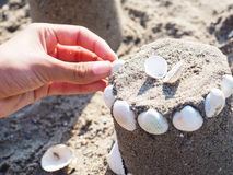 Person making sand castle with clams Royalty Free Stock Photography