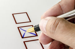 Person Marking in a Checkbox on white paper. Stock Images
