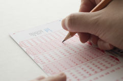 Person marking number on lottery ticket with pen Royalty Free Stock Photos