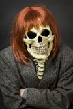Person in mask of death and red wig Royalty Free Stock Photography