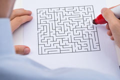 Person With Maze On Paper. Close-up Of Person Hand With Maze On Paper And Red Marker Royalty Free Stock Photos