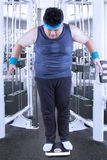 Person measuring his weight. Fat man measuring his weight in the fitness center Royalty Free Stock Images