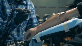 Person med den konstgjorda handen som får en tatuering, bionisk protes stock video