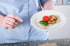 Person med en smörgås på en platta Fotografering för Bildbyråer