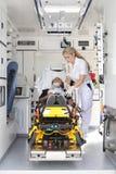 Person med paramedicinsk utbildning i en ambulansbil som ger första hjälpen Royaltyfria Bilder