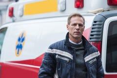 person med paramedicinsk utbildning i tillfällig kläder som framme står av ambulansen och att se Arkivbild