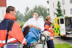 Person med paramedicinsk utbildning med tålmodign på stretcherambulanshjälpmedel Arkivbild