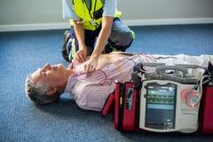 Person med paramedicinsk utbildning som använder en yttre defibrillator på en medvetslös patient Royaltyfri Foto