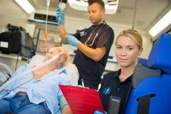 Person med paramedicinsk utbildning som behandlar den medvetslösa mannen i ambulans Royaltyfri Foto