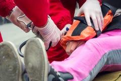 Person med paramedicinsk utbildning som hjälper en sårad flicka Royaltyfri Fotografi